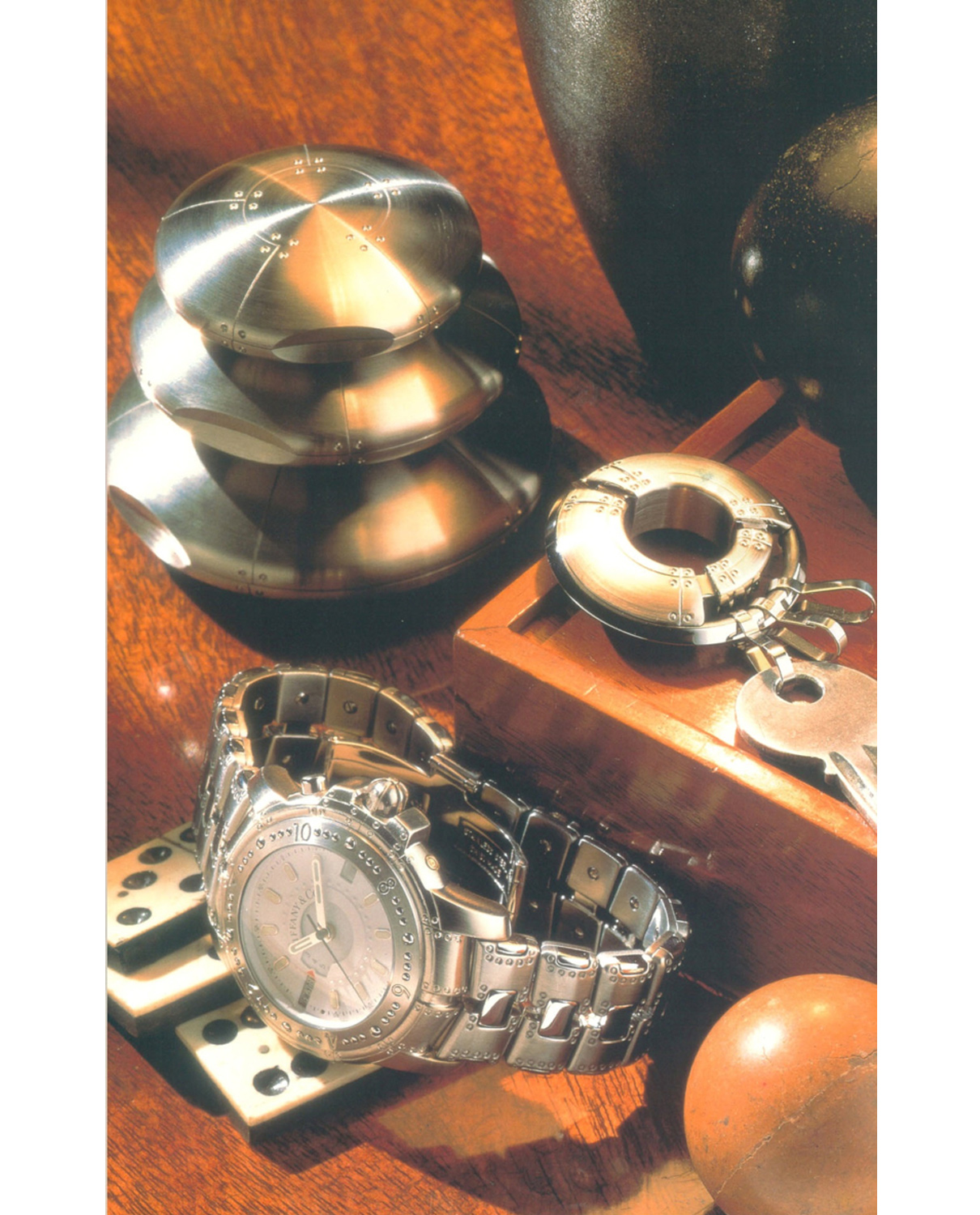 Loring's 1997 Book: Tiffany's 20th Century: A Portrait of American Style. Perisphere Nesting Boxes in three sizes, Porthole Keychain, and World Time Wristwatch with Stainless Steel Band.