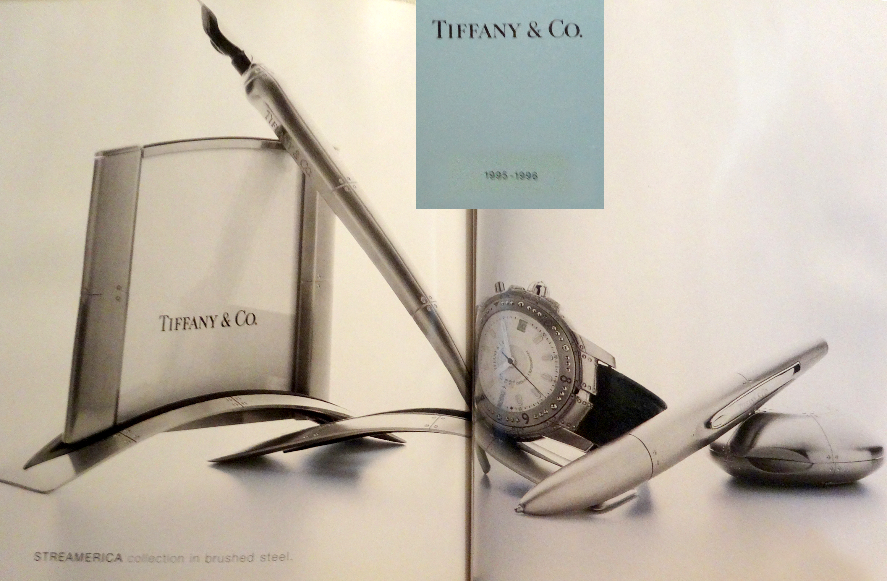 A Page from a 1995 Tiffany & Co. Blue Catalog showcasing Streamerica Stainless Steel Airframe Picture Frame Medium, Airframe dipping ink pen with stand, Automatic Watch with leather band, Ballpoint Pen, and Perisphere Nesting Box.
